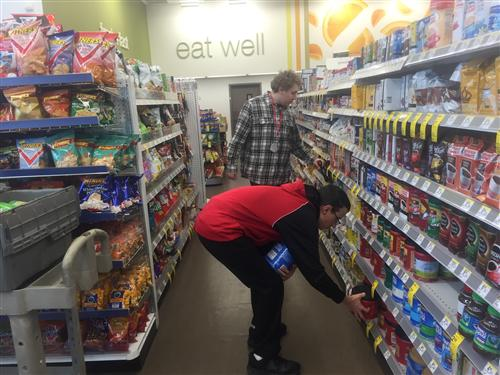 students stocking shelves at a grocery store